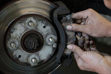 Mechanic servicing brakes of car